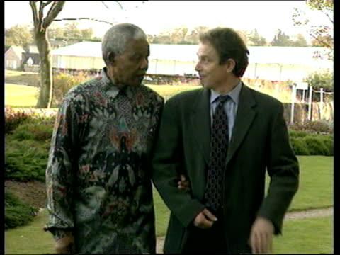 vídeos y material grabado en eventos de stock de south african president nelson mandela and prime minister tony blair walk arm in arm commonwealth conference scotland 25 oct 97 - primer ministro británico