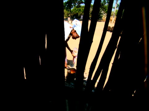 South African woman stirs cooking pot behind silhouetted fence South Africa