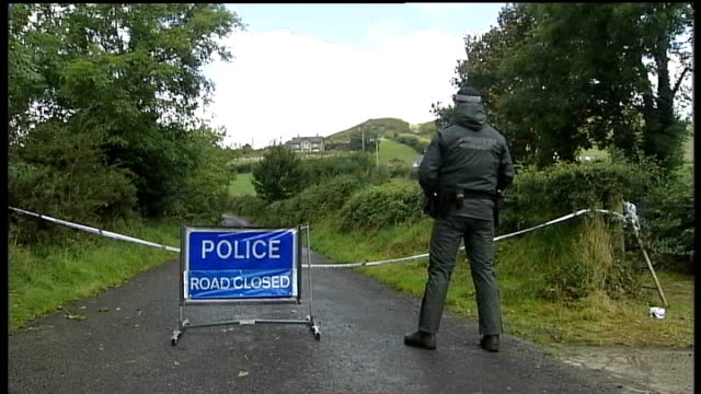 Forkhill EXT Armed police officer patrolling site where a large bomb was discovered 'Road Closed' sign Police and troops boarding Chinook helicopter...