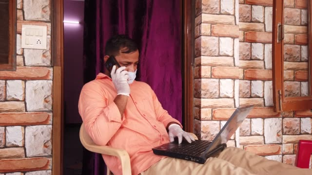 south asian man sitting at home working on his laptop for online work for his business social networking talking on smart phone mobile device at the comfort of his home - infectious disease stock videos & royalty-free footage