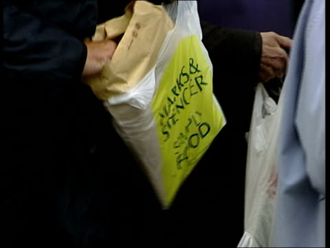 royal festival hall: ext/wet marks & spencer shareholders queuing to enter the agm cms marks & spencer bag containing documents, held sign 'agm' with... - ロイヤルフェスティバルホール点の映像素材/bロール