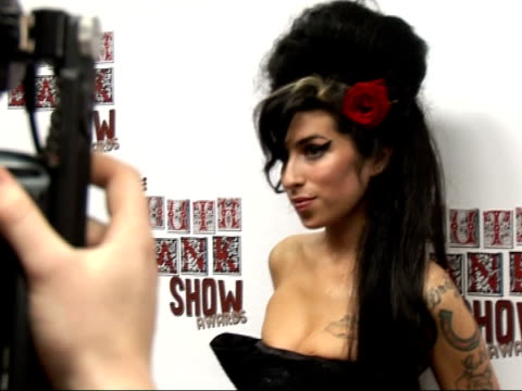 south bank show awards: photocall and interviews; **beware flash photography** amy winehouse posing for photocall as pulls up her dress **ends** - amy winehouse stock-videos und b-roll-filmmaterial