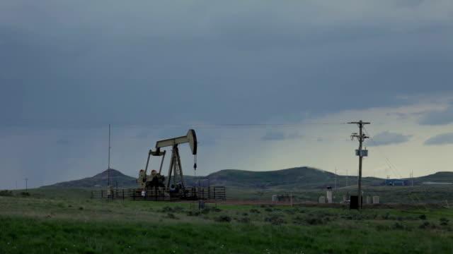south dakota stormy prairie oil pump jack flare stack pollution - pump jack stock videos & royalty-free footage