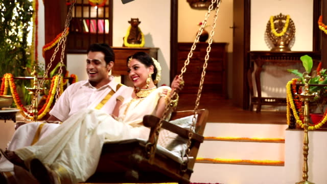 South indian couple swinging on porch swing, Delhi, India