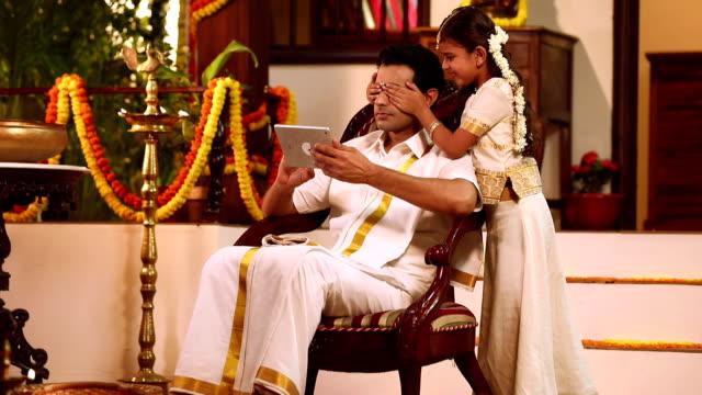 vidéos et rushes de south indian man working on digital tablet with her daughter, delhi, india - prendre sur les genoux