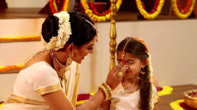 vídeos y material grabado en eventos de stock de south indian woman applying tika to her daughter in onam festival, delhi, india - esmalte de uñas rojo