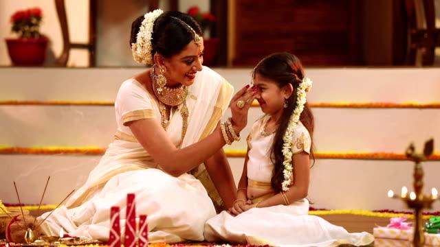 vídeos y material grabado en eventos de stock de south indian woman celebrating onam festival with her daughter, delhi, india - esmalte de uñas rojo