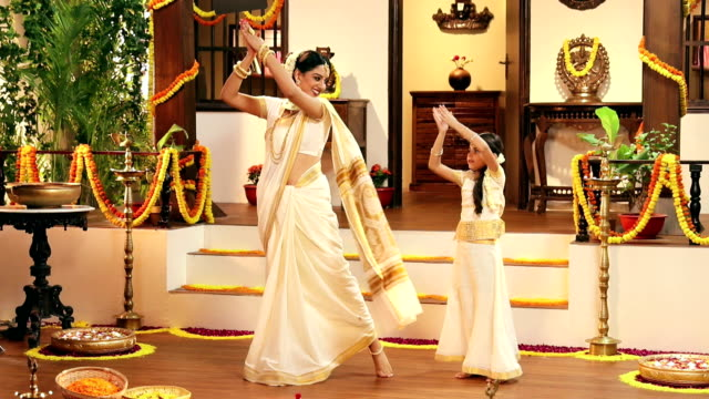 South Indian woman dancing with her daughter in onam festival, Delhi, India