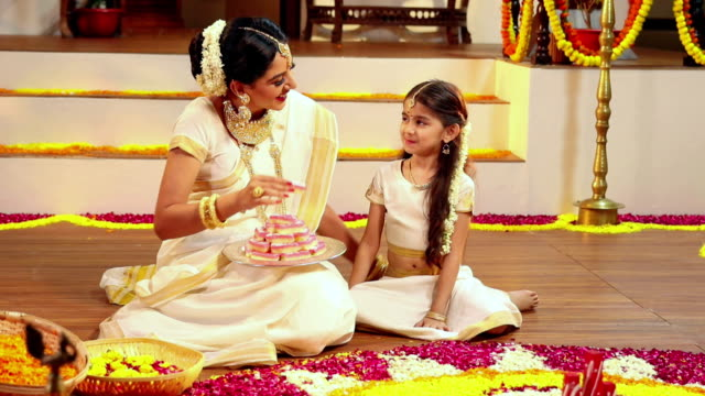 south indian woman eating sweets with her daughter in onam festival, delhi, india - bracelet stock videos and b-roll footage
