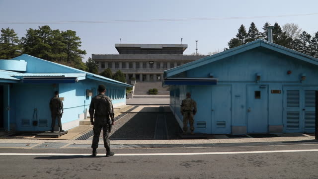 stockvideo's en b-roll-footage met south korean and us soldiers stand guard next to united nations command military armistice commission conference buildings at the truce village of... - south korean army