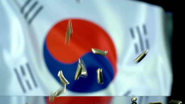 south korean flag behind bullets falling in slow motion - south korean flag stock videos & royalty-free footage