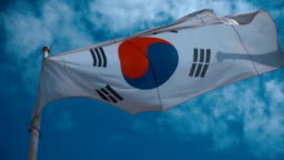 South Korean flag on the flagpole waving in the wind against a blue sky