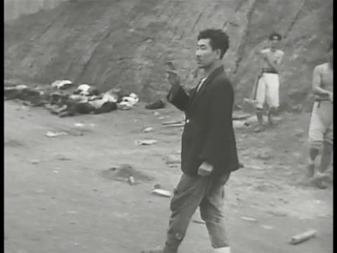 south korean male counting row of bodies, dead people, unidentified soldiers or civilians, lying side-by-side on roadside. bombed structure. people... - grief stock videos & royalty-free footage