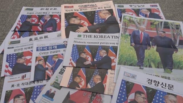 south korean newspapers front pages are dominated by photos of the historic handshake between us president donald trump and north korean leader kim... - g8:s toppmöte bildbanksvideor och videomaterial från bakom kulisserna