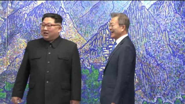 South Korean president Moon Jaein and North Korean leader Kim Jongun are shaking hands after issuing a joint statement in the Peace House building at...