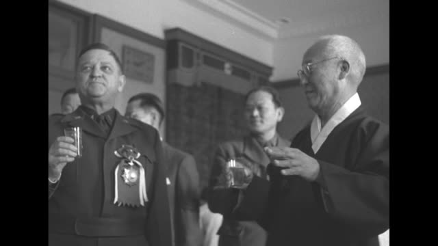 VS South Korean President Syngman Rhee and US Lt Gen Walton Walker stand together at Rhee's residence in Seoul as drinks are handed out after Rhee...