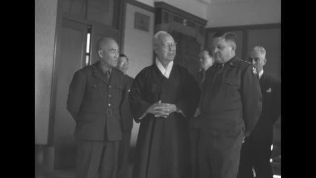 South Korean President Syngman Rhee stands with US Lt Gen Walton Walker and others in room / VS unid Rhee Walker / montage Rhee reads citation Walker...