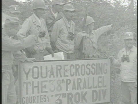 south korean soldiers walking along on road advancing north crossing the 38th parallel soldiers waving putting up flags of south korea celebrating w/... - parallelo video stock e b–roll