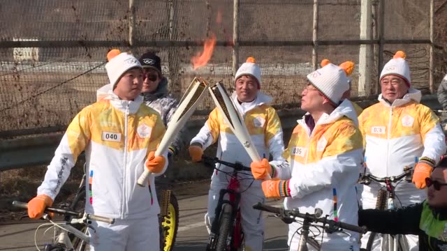 South Korean torchbearers carry the Olympic flame across the Unification Bridge near the Demilitarised Zone that has divided the peninsula since the...
