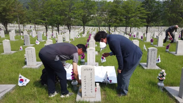 south koreans visit at the gravestone of their relative who died during the korean war during a 65th anniversary of the memorial day amid coronavirus... - cemetery stock videos & royalty-free footage