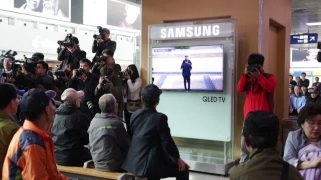 south koreans watching a tv screen at seoul station clap when the leaders of north and south korea shake hands - korean ethnicity stock videos & royalty-free footage