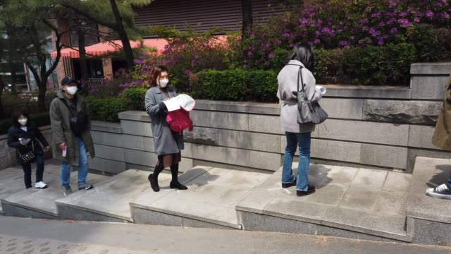 south koreans wear masks and stand according to social distancing as a preventive measure against the coronavirus as they prepare for an insurance... - korean ethnicity stock videos & royalty-free footage