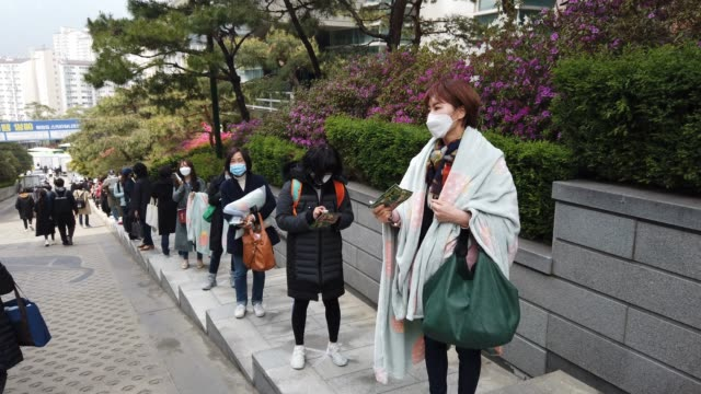 south koreans wear masks and stand according to social distancing as a preventive measure against the coronavirus as they prepare for an insurance... - schulische prüfung stock-videos und b-roll-filmmaterial