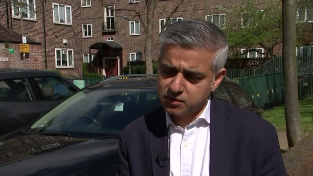 south london: earlsfield: henry prince estate: ext set-up shots of reporter walking with sadiq khan mp 'henry prince' clock on wall sign for 'henry... - ニナ・ホサイン点の映像素材/bロール