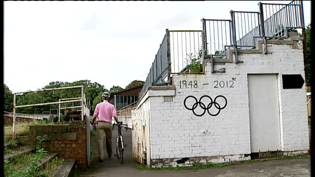 stockvideo's en b-roll-footage met south london herne hill ext reporter to camera as along on bike '1948 2012' and olympic rings painted on wall grass growing inside velodrome broken... - lycra