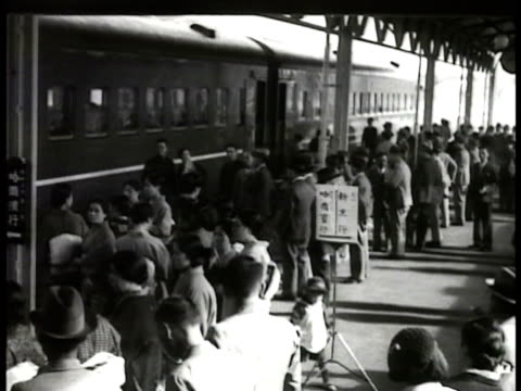 south manchuria railway locomotive sitting. sign for dairen in japanses & english . people waiting for train in station steam under standing train... - showa period stock videos & royalty-free footage