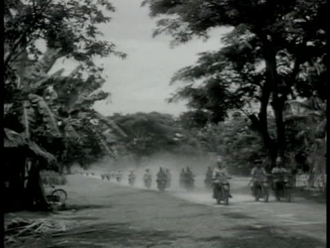 south pacific countryside trees mountains . sikh soldiers on motorcycles passing through forest road. native sikhs watching motorcyclist & convoy.... - south pacific ocean点の映像素材/bロール