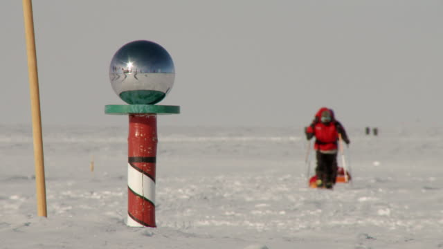 ms of south pole marker reflecting flags with two people on skis approaching / south pole, antarctica - south pole stock videos and b-roll footage