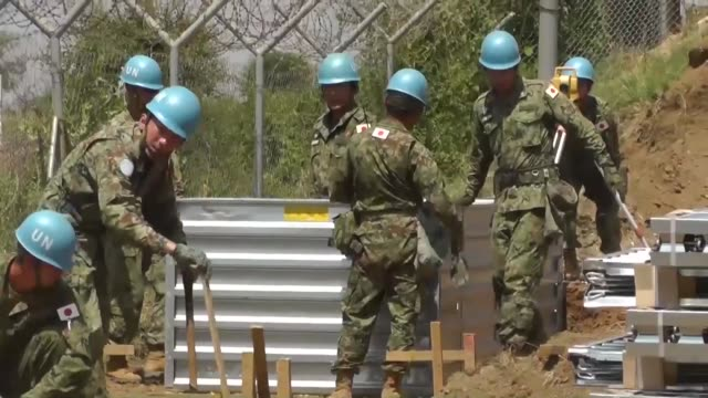 japanese ground selfdefense force personnel work to set up safety shields between the peacekeeping operation headquarters and nearby refugee camp in... - 平和維持点の映像素材/bロール