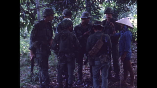 south vietnam and us soldiers question and search a woman villager who has severe burn marks on one arm. - 南ベトナム点の映像素材/bロール