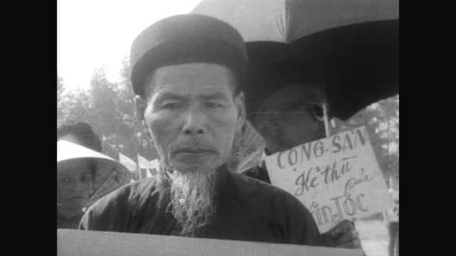south vietnamese demonstrate against viet cong attacks / huge crowd holding banners in vietnamese / women dressed similarly in sedge hats and young... - ベトコン点の映像素材/bロール
