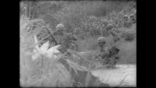 south vietnamese rangers waling through field as helicopters fly overhead / black smoke rises from the jungle / troops wade through river / exchange... - south vietnam stock videos & royalty-free footage