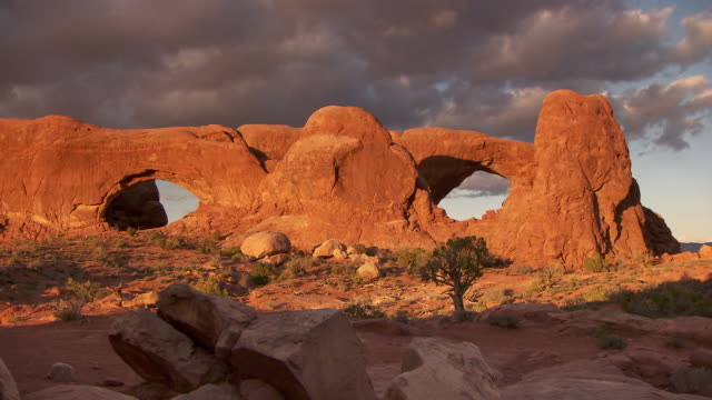 South Window Arch and North Window Arch at sunset with dramatic sky and clouds