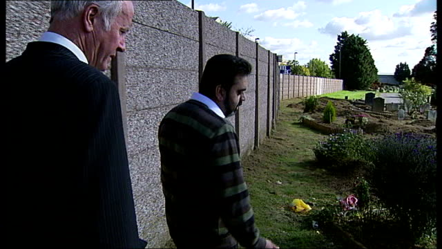 Southall cemetery vandalised Muslim men praying beside grave Broken container on ground Container of slug killer on ground Flowers strewn on ground...