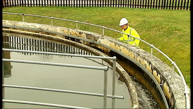 vídeos y material grabado en eventos de stock de southampton to have fluoridated water supplies; england: hampshire: southampton: ext inspector looking at water in sedimentation tank at water... - hampshire