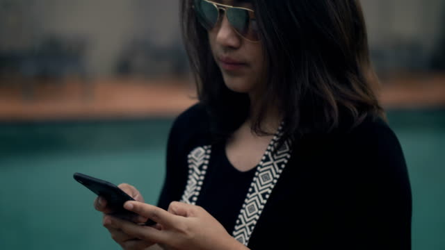 vídeos de stock, filmes e b-roll de sudeste asiático: empresária usando telefone no jardim - 40 49 anos