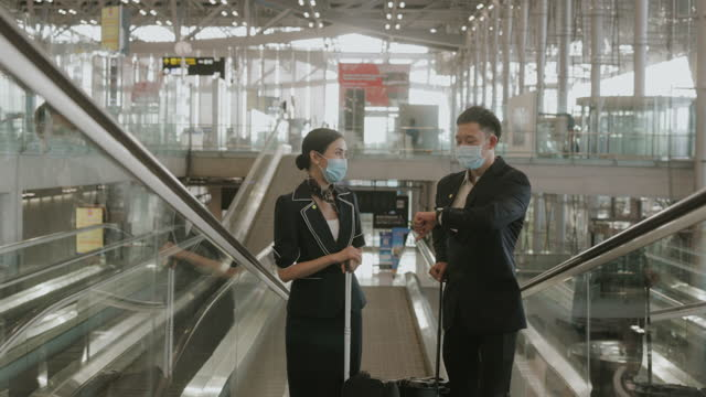 southeast asian cabin crew couple at the airport-stock video - safety stock videos & royalty-free footage
