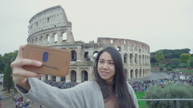 southeast asian couple take a sight seeing and selfie in front of colosseum, italy - roman stock videos & royalty-free footage