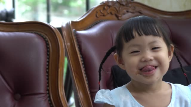 東南アジアの女の子はアイスクリームを食べることに非常に満足しています。
