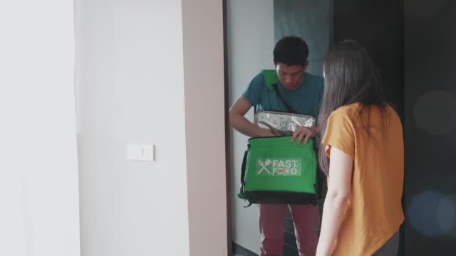 東南アジアの男性は、ドアからドアサービスに顧客に食べ物を提供します - 受ける点の映像素材/bロール