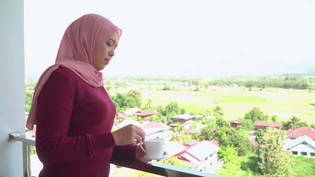 southeast asian mid-muslim woman with winter cloth,  hijab walking on balcony to looking at forest with feeling happiness, relaxation, enjoyment with cup of tea in the hotel. concept of travel, hobby, loving adventure, explorer, and alone at nature. - loving cup stock videos & royalty-free footage