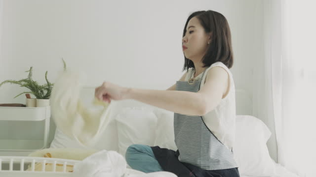 southeast asian woman folding their cloth on weekend - bedclothes stock videos & royalty-free footage