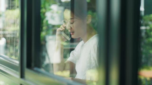 stockvideo's en b-roll-footage met zuidoost-aziatische vrouw is het gebruik van telefoon bij de bibliotheek naast de tuin - mid volwassen