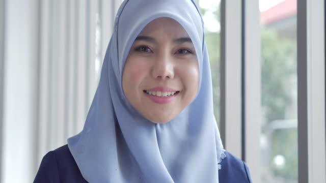vidéos et rushes de jeune femme d'affaires musulmane d'asie du sud-est regardant l'appareil-photo souriant heureux utilisant le foulard traditionnel. portraits d'hommes et de femmes musulmans - partie médiane
