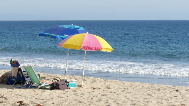 southern california malibu beach two colorful umbrellas and two empty beach chairs on the sand coolers and other articles no people surf washing up... - cool box stock videos & royalty-free footage