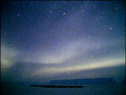 southern lights (aurora australis) light up the night sky and snowy landscape in blinding white light streaking across the sky lighting up the antarctic setting, penguins in large group on snow - antarctica night stock videos & royalty-free footage